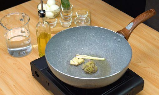 Bumbu halus, bawang putih, serai ditumis di atas wajan menggunakan sedikit minyak.