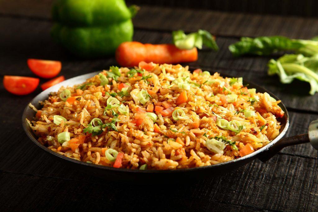 Sepiring nasi goreng tersaji di atas piring hitam yang beralaskan taplak hitam dan didampingi berbagi potongan sayuran.