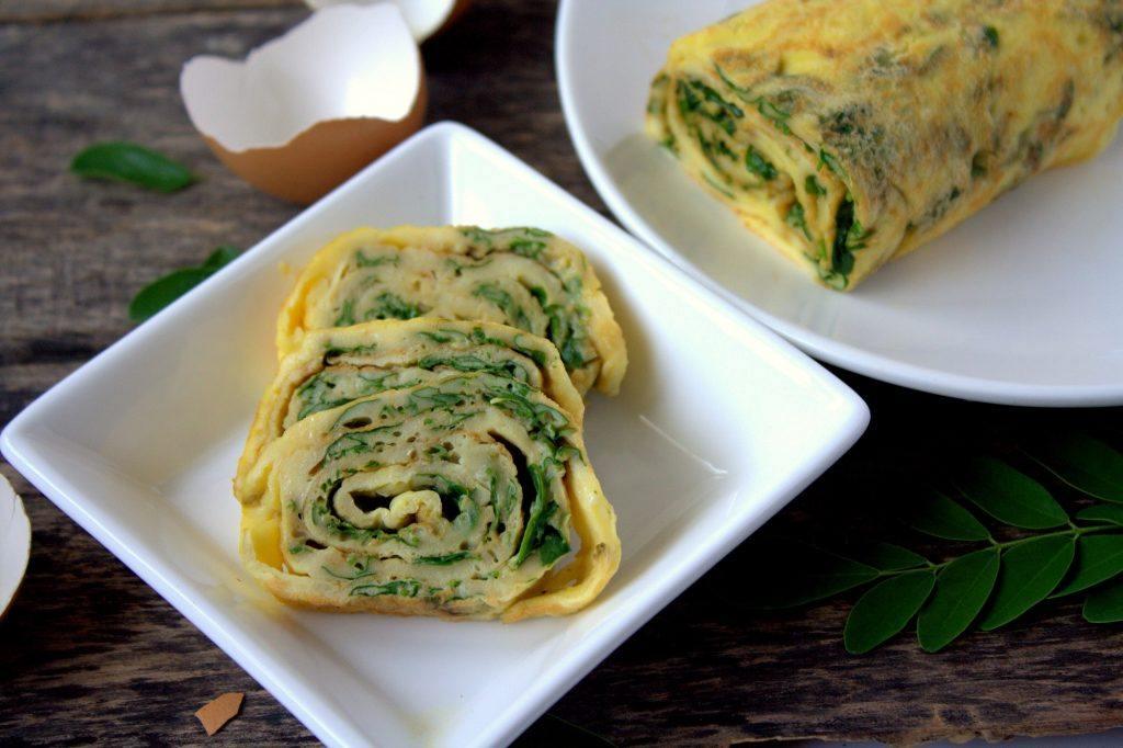 Telur gulung daun kelor dipotong dan disajikan di atas piring putih.