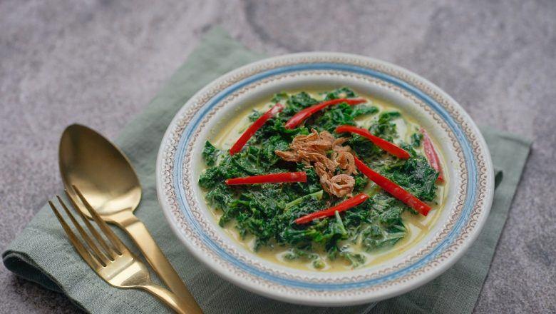 Seporsi gulai daun singkong tersaji dalam mangkuk dan didampingi alat makan emas.