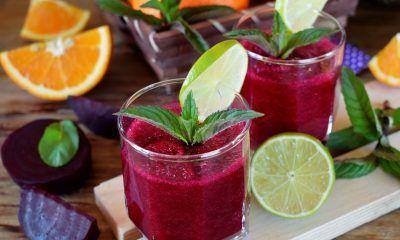 Segelas jus buah bit tropikal tersaji bersama buah bit, potongan jeruk, serta lemon.