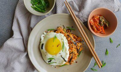 Sepiring nasi goreng sederhana dengan telur mata sapi dan sumpit.