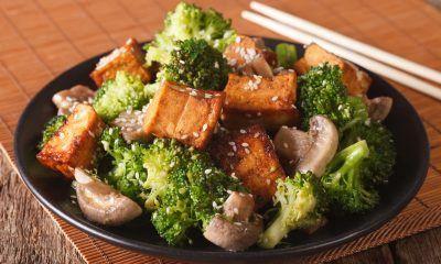 Sepiring tumis brokoli dan tahu putih tersaji di atas meja kayu.