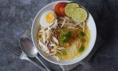 Semangkuk hasil memasak resep soto kuning lengkap dengan telur rebus dan jeruk nipis, dan sendok garpu di sampingnya.