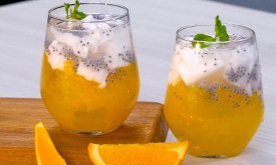 Dua gelas es kelapa muda dengan jelly jeruk diletakkan di atas talenan.