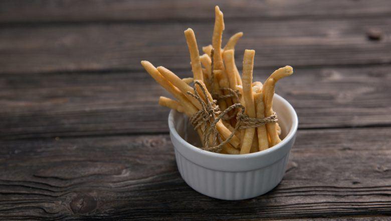 Mangkuk kecil berisikan hasil resep kue bawang keju yang diikat dan diletakkan di atas meja kayu.