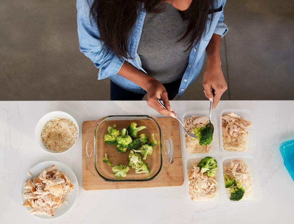 Seorang wanita tengah menyiapkan meal prep di meja dapur