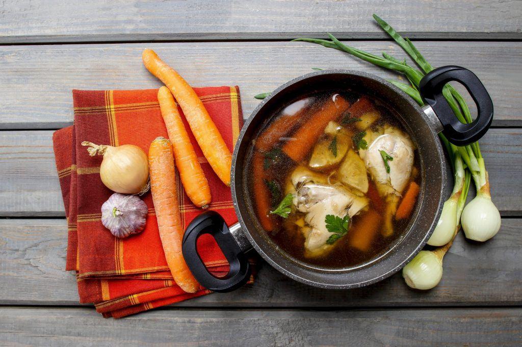 Menu buka puasa praktis berupa sepanci sup ayam dengan bahan-bahan masakan di sekitarnya.