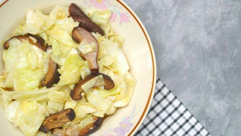 Sepiring tumis sawi putih dengan jamur shiitake tersaji di atas meja batu.