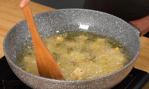 Menggoreng tempe untuk resep tumis tempe kecap manis dalam minyak panas.