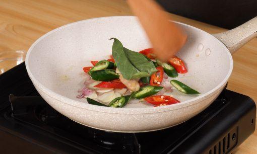 Menumis dedaunan aromatik dan cabai untuk resep tumis tempe kecap manis.