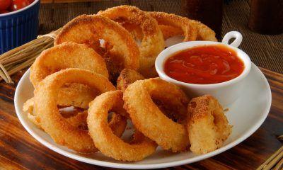 Hasil masak resep onion ring tersaji di atas piring putih beserta saus tomat.