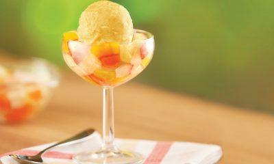 Segelas tinggi berisi potongan buah dan nata de coco serta es krim yang dinamakan Fresh Mango Frutilicious.
