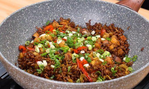 Menggoreng nasi dengan taburan bawang untuk resep nasi goreng ikan asin.
