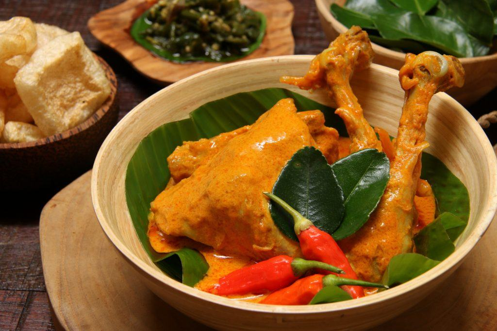 Sepiring masakan gulai ayam Padang dengan sambal hijau di belakangnya.
