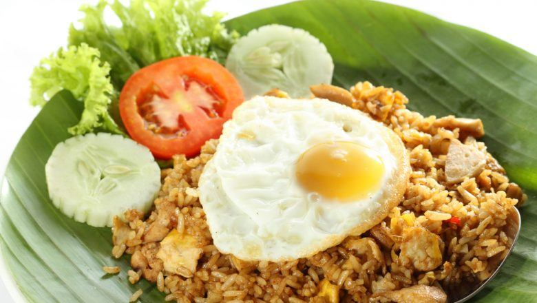 Sepiring hasil masak resep nasi goreng pedas yang dialasi daun pisang lengkap dengan telur mata sapi.