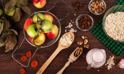 Sepiring apel dikelilingi dengan makanan sehat untuk diet setelah Lebaran.