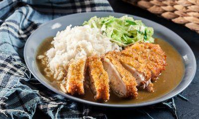 Ayam katsu kari tersaji dengan sayuran di atas piring.