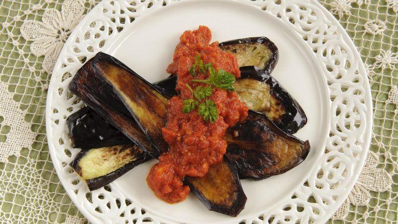 Terong goreng sambal teri tersaji di atas piring putih.