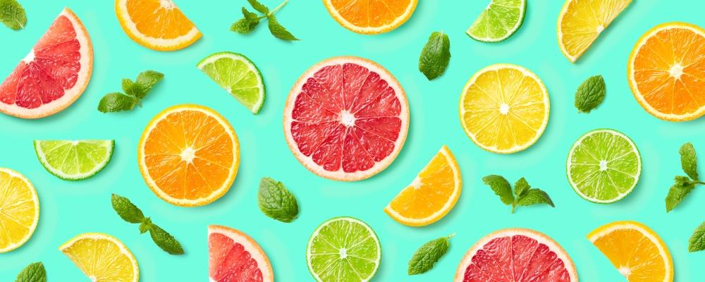 Berbagai potongan citrus, makanan rendah kolesterol, diletakkan di atas papan hijau.