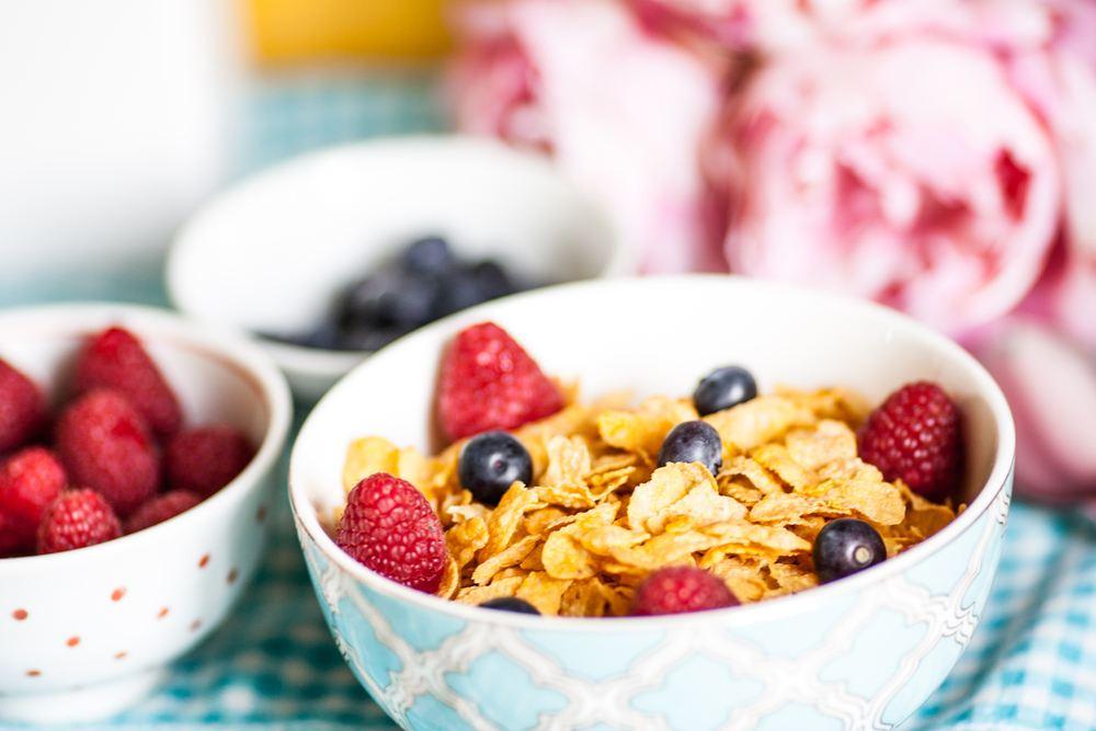 Semangkuk sereal berisikan buah-buahan beri dan bersanding dengan mangkuk lainnya.