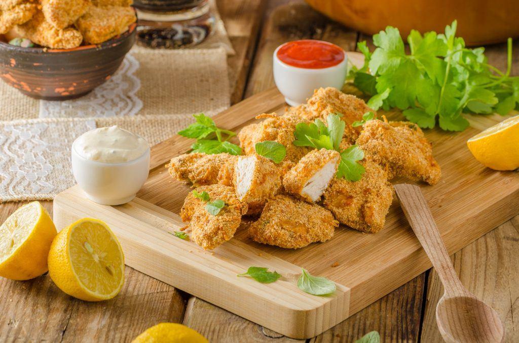 Chicken popcorn di atas piring kayu dan saus sambal di belakangnya dengan buah lemon dan saus tartar mengelilinginya.