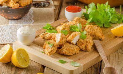 chicken pop corn di atas piring kayu dan saus sambal di belakangnya.