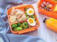 Menu bekal makan siang dalam kotak warna oranye berisi makanan sehat.