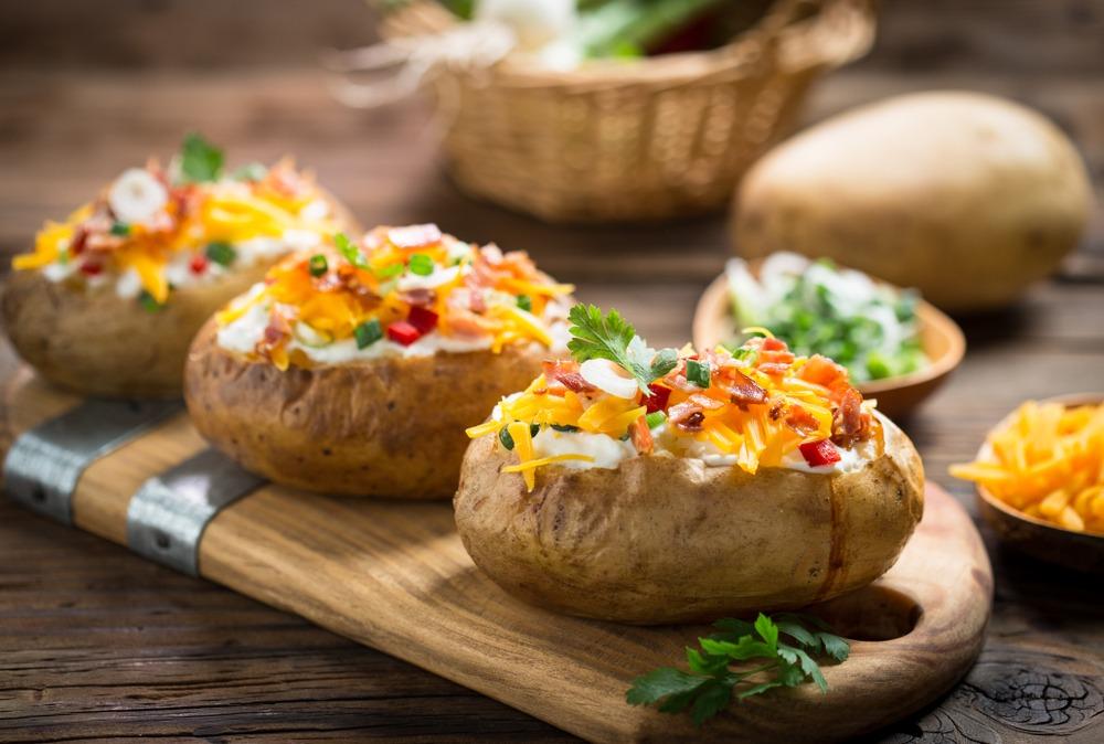 Tiga buah baked potato tersaji di atas talenan.