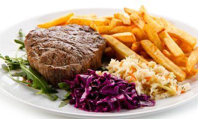 Sepiring steak dan olahan kentang goreng dengan sayuran.