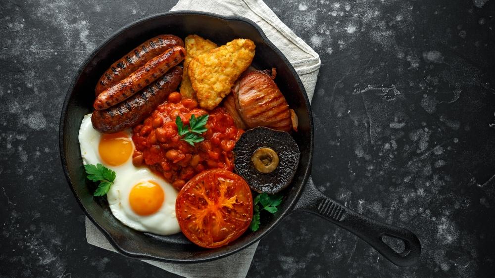Hash brown dalam wajan tersaji dengan sosis, tomat, jamur, kacang, dan telur.