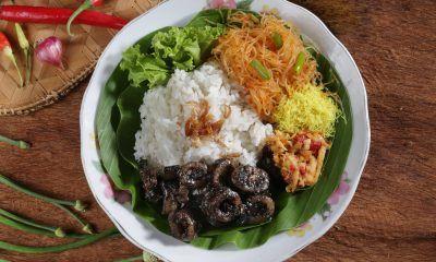 Hasil masak resep cumi hitam disandingkan dengan nasi rames disajikan di atas piring beralaskan daun pisang.