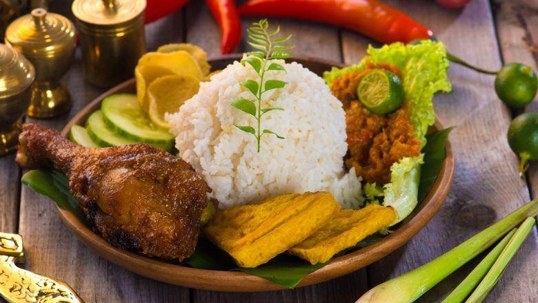 Ayam ungkep tersaji bersama nasi putih dan lalapan.