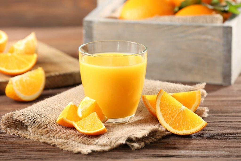 Segelas jeruk hangat segar didampingi potongan buah dan disajikan di atas napkin serta meja kayu.