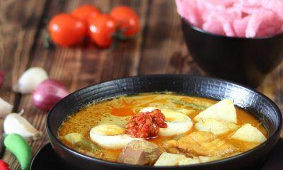 Semangkuk Ketupat Sayur Padang dengan pelengkap.