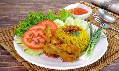 Seporsi nasi briyani tersaji bersama ayam di atas piring putih dan tatakan bambu.
