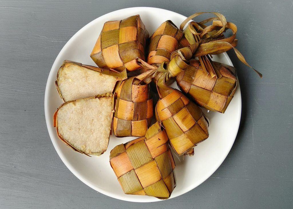 Beberapa ketupat dalam piring putih, salah satunya telah terpotong, hasil dari cara memasak ketupat agar tidak cepat basi.