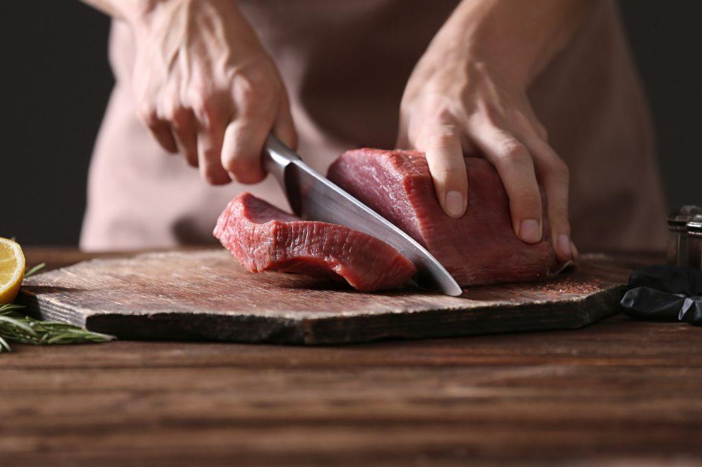 Tangan chef memotong daging di atas talenan dengan pisau