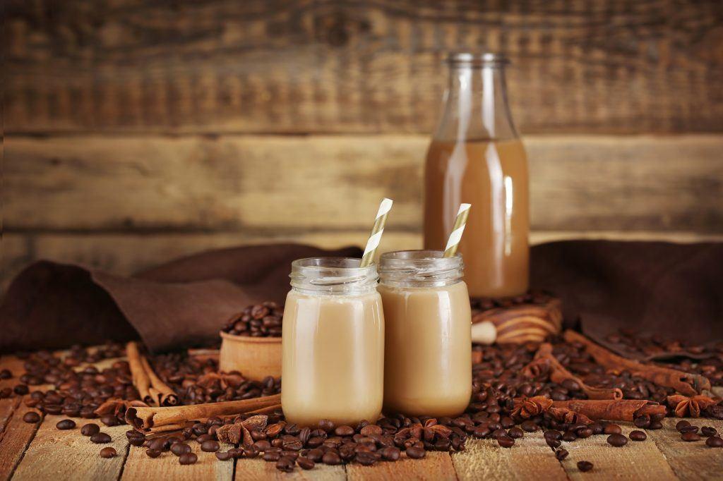Dua gelas kaca berisi es kopi susu 1 liter dengan botol berisi kopi di belakangnya.