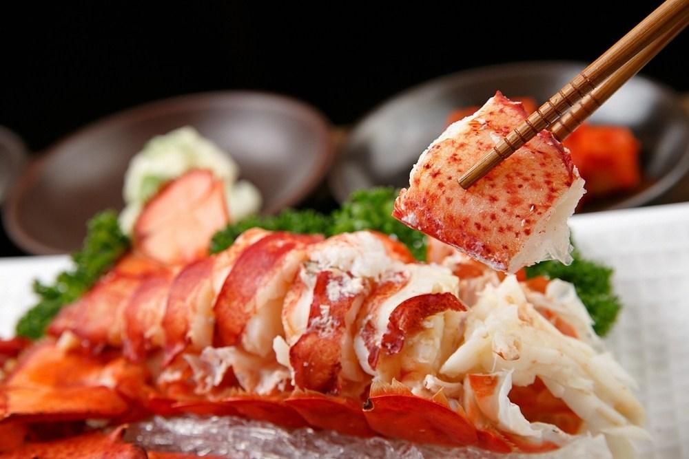 Masak lobster kukus tengah dinikmati dengan menggunakan sumpit.