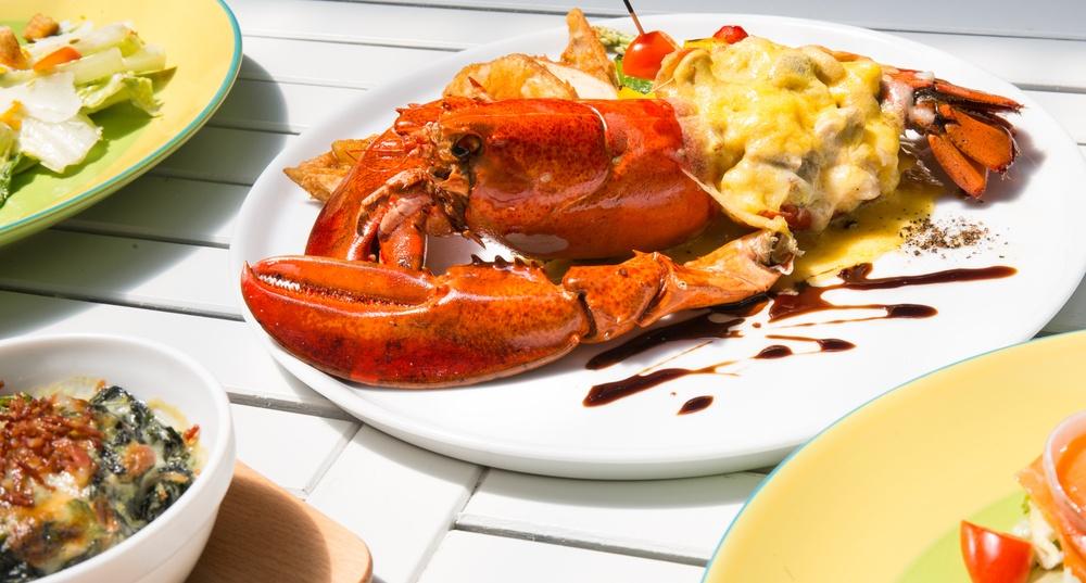 Hasil masak lobster thermidor tersaji bersama salad di atas piring.