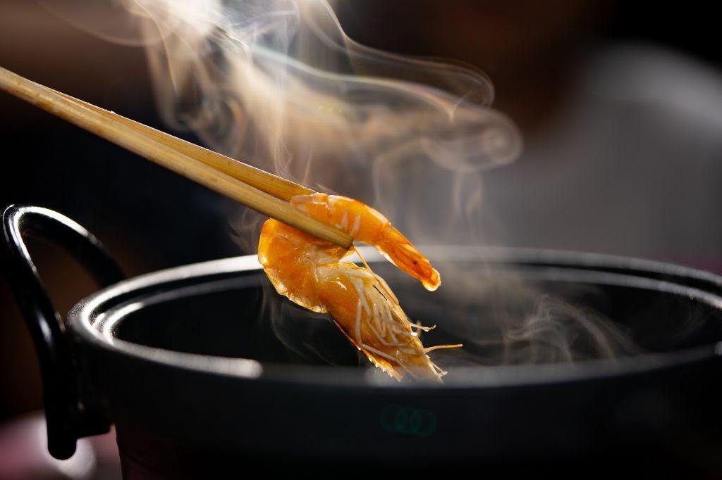 udang diambil dengan sumpit dari panci