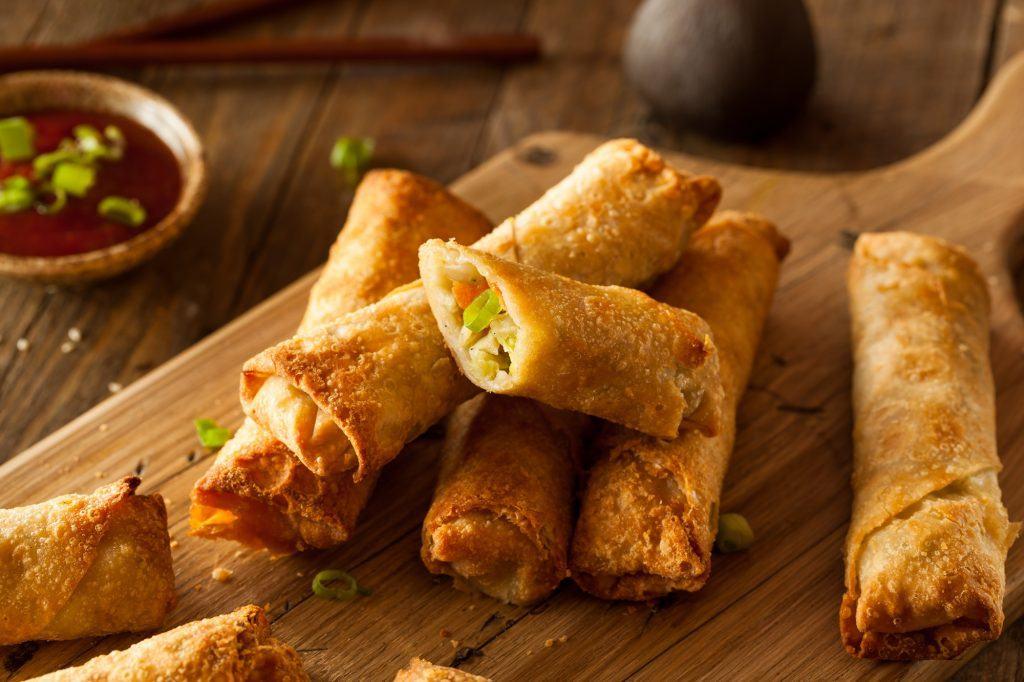 Resep camilan simpel dalam bentuk beberapa lumpia isi sayur di atas piring kayu.