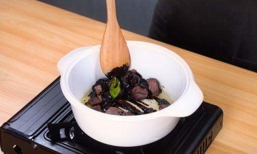 Bumbu rawon tengah dicampurkan dengan daging dalam panci.