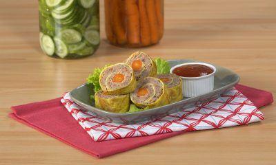 Seporsi hasil masak resep rolade daging sapi disajikan di atas meja kayu bersama sambal.