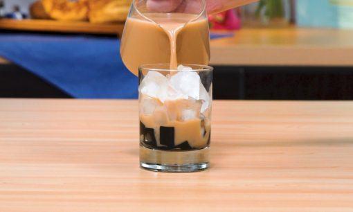 Mengisikan milk tea ke dalam gelas berisi jelly.