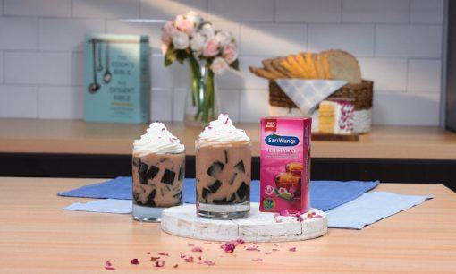 Milk tea jelly disajikan di atas meja kayu dan taburan kembang mawar.