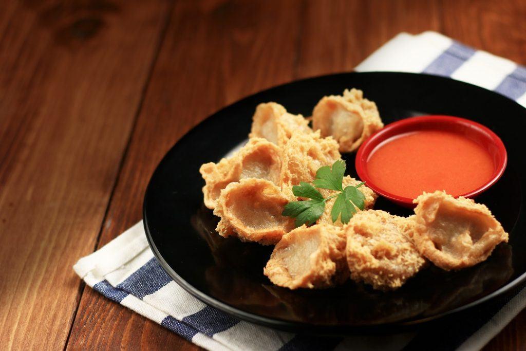 Tahu walik dengan cocolan Saus Sambal Jawara disajikan di atas taplak dan meja kayu.