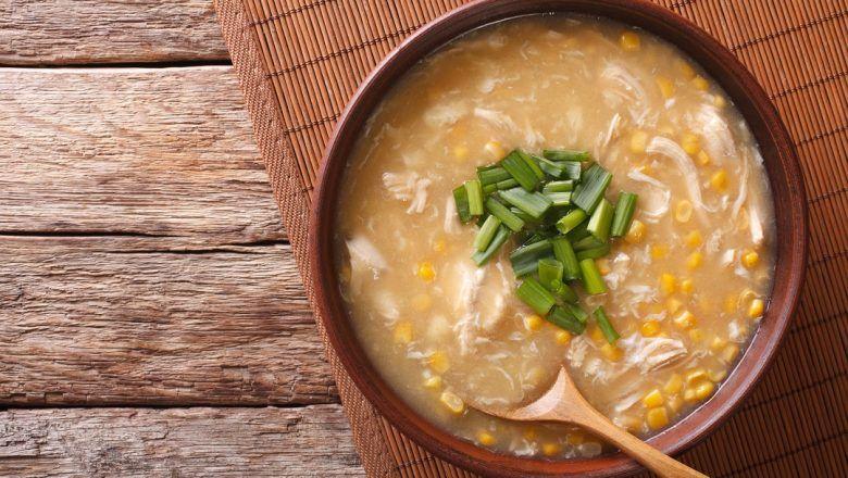 Binte biluhuta disajikan dalam mangkuk dan didampingi sendok kayu, diletakkan di atas meja kayu.
