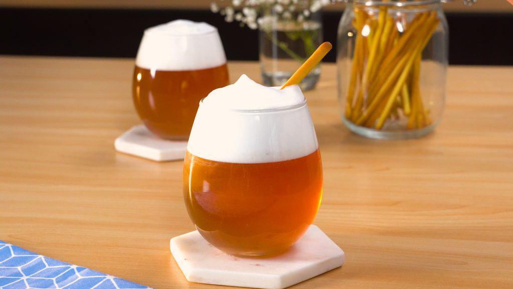 Dua gelas resep minuman kekinian cheese tea disajikan di atas meja kayu.